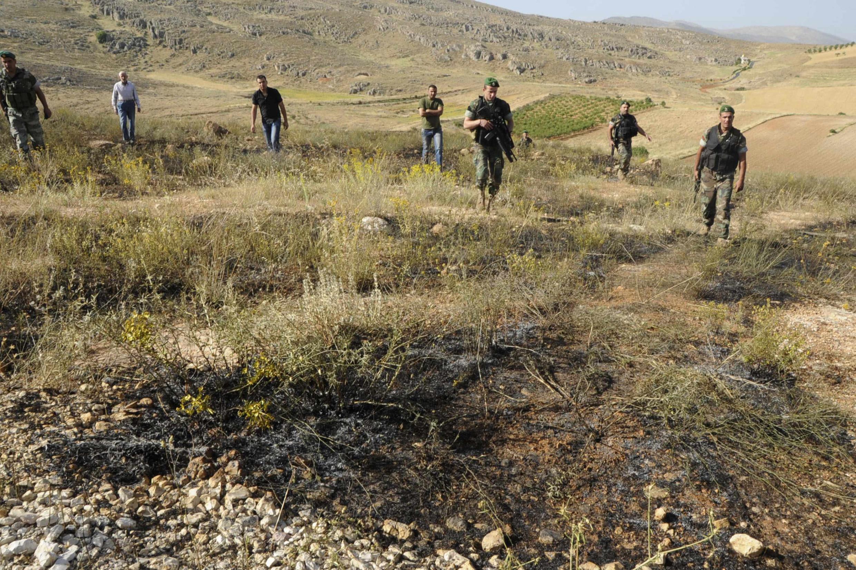 Soldados libaneses inspecionam local atingido por ataques vindos da Síria.