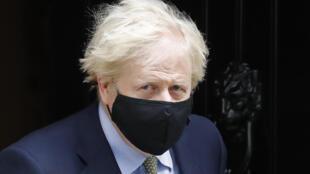 Boris Johnson sale con mascarilla de su residencia oficial del número 10 de Downing Street para asistir a la sesión semanal de control en el Parlamento británico, el 14 de octubre de 2020 en Londres