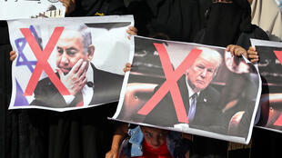 Palestinian women hold crossed-out posters depicting US President Donald Trump and Israeli prime minister Benjamin Netanyahu during a protest against Bahrain's workshop for peace.