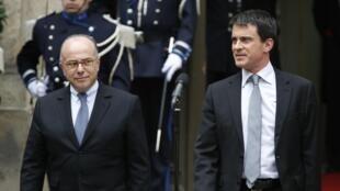 Passation de pouvoir entre Manuel Valls (D) le nouveau Premier ministre et ministre de l'Intérieur sortant et le nouveau ministre de l'Intérieur Bernard Cazeneuve. Paris, le 2 avril 2014.