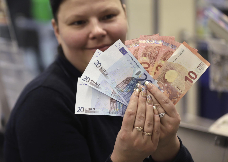 Funcionária de um banco em Vilnius, na Lituânia, mostra notas de euro, que se tornou a moeda oficial do país nesta quinta-feira (1°).