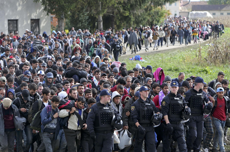 Grupo de migrantes sendo conduzido pela polícia em Brezice, Eslovênia, 20 de outubro de 2015.