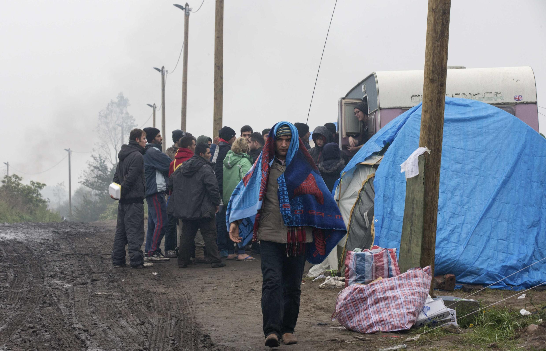 Migrants queue as volunteers distribute sleeping bags in the makeshift camp in Calais, 16 October 2015.