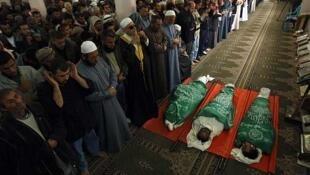 Palestinos oran junto a los cuerpos de militantes de Hamas abatidos por el ejéricito israelí. El 8 de abril de 2011 en la franja de Gaza.