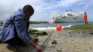 A Kenyan boy looks at a cable in Mombasa. This cable improves information and communication technology.