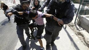 Polícia israelense detém criança palestina durante protestos durante o Dia da Nakba, na região leste de Jerusalém, nesta terça-feira.