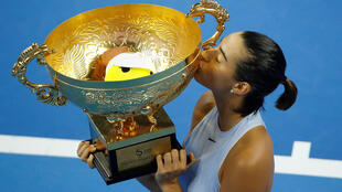 Caroline Garcia kisses the trophy after winning the China Open final against Simona Halep.