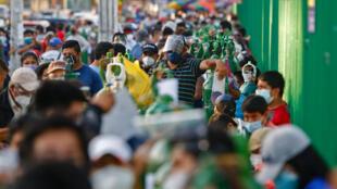 People wait in long lines to get medical oxygen in San Juan de Lurigancho, near Lima, Peru