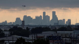 A helicopter hovers above the Houston skyline as sunlight breaks through storm clouds from Tropical Storm Harvey in Texas, U.S. August 29, 2017