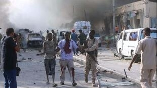 soldado somali evacua um homem ferido do local da explosão, em Mogadíscio, no dia 14 de Outubro de 2017na em the scene of explosion in Mogadishu