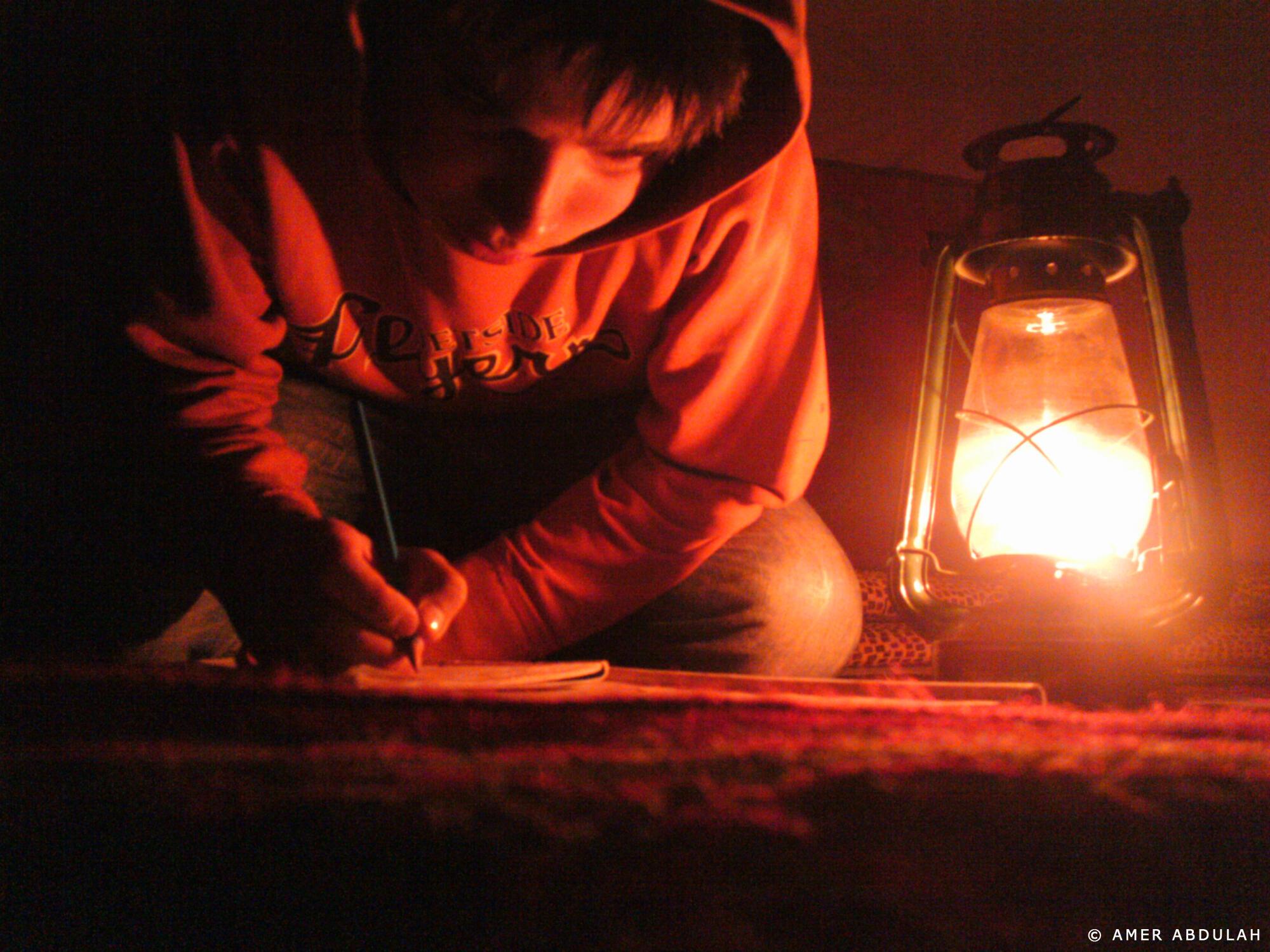Dans l'intimité de la tente, un enfant fait ses devoirs alors que l'obscurité est tombée sur le camp.