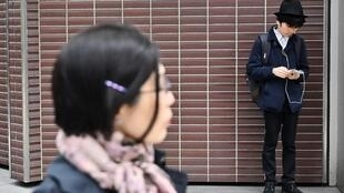 Un jeune homme utilise son «smartphone» dans les rues de Tokyo. (Image d'illustration)