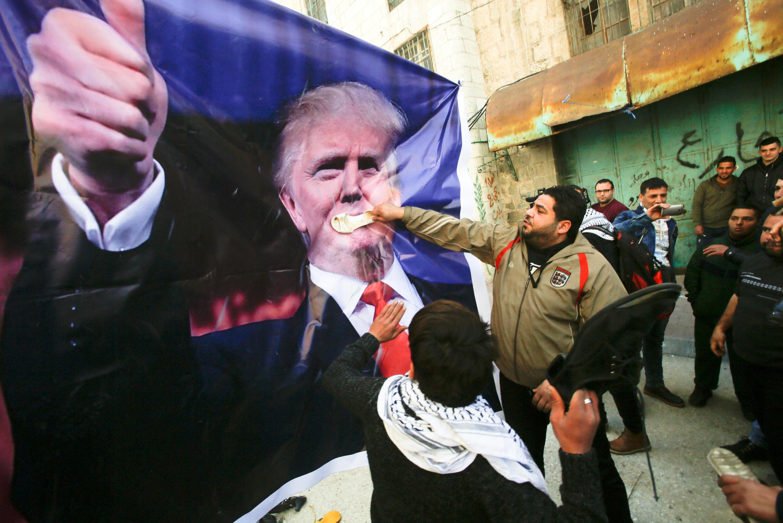 Người dân Palestine ném giầy vào ảnh chân dung cỡ lớn của Donald Trump trong một cuộc biểu tình tại thành phố Hébron, Cisjordanie, ngày 24//2017.