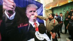 Des Palestiniens jettent des chaussures sur un portrait géant du président américain pendant une manifestation dans la ville d'Hébron en Cisjordanie, le 24 février 2017.