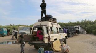 Un homme attend d'autres passagers, dressé sur le toit d'une camionnette pleine de réfugiés venus de Gambie.