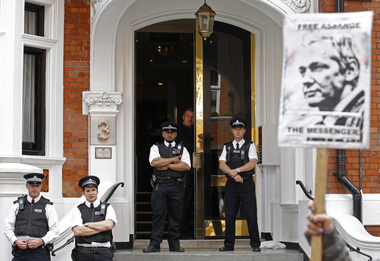 Người ủng với ảnh Julian Assange, trước đại sứ quán Ecuador được canh gác cẩn mật tại Luân Đôn. Ảnh ngày 17/08/2012. Julian Assange tỵ nạn tại đây từ tháng 6/2012
