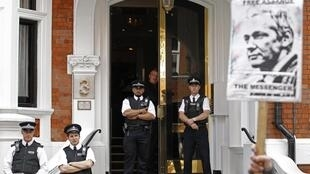 Fachada da embaixada equatoriana em Londres tem cartaz de apoio a Julian Assange e dezenas de policiais