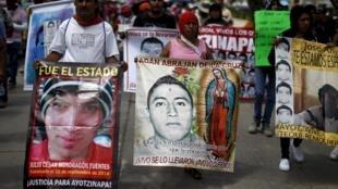 Les familles des étudiants d'Ayotzinapa manifestent en brandissant les portraits des 43 élèves disparus en septembre 2014.