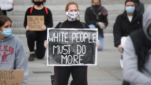 A woman wearing a protective face mask kneels as she holds a sign during a Black Lives Matter protest in Trafalgar Square in London, following the death of George Floyd who died in police custody in Minneapolis. London, Britain, June 5, 2020. REUTERS/Toby Melville