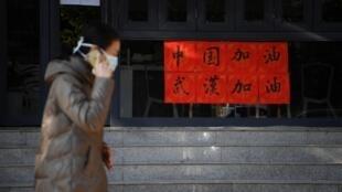 Une femme portant un masque passe devant un coffee shop à Kunming, dans la province du Yannan, le 2 février 2020, en Chine où le pays a décidé de fermer des milliers de ces boutiques pour éviter la propagation du 2019-nCoV.