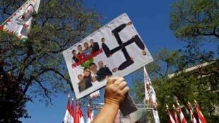 Manifestante empunha cartaz que faz alusão a símbolo nazista.