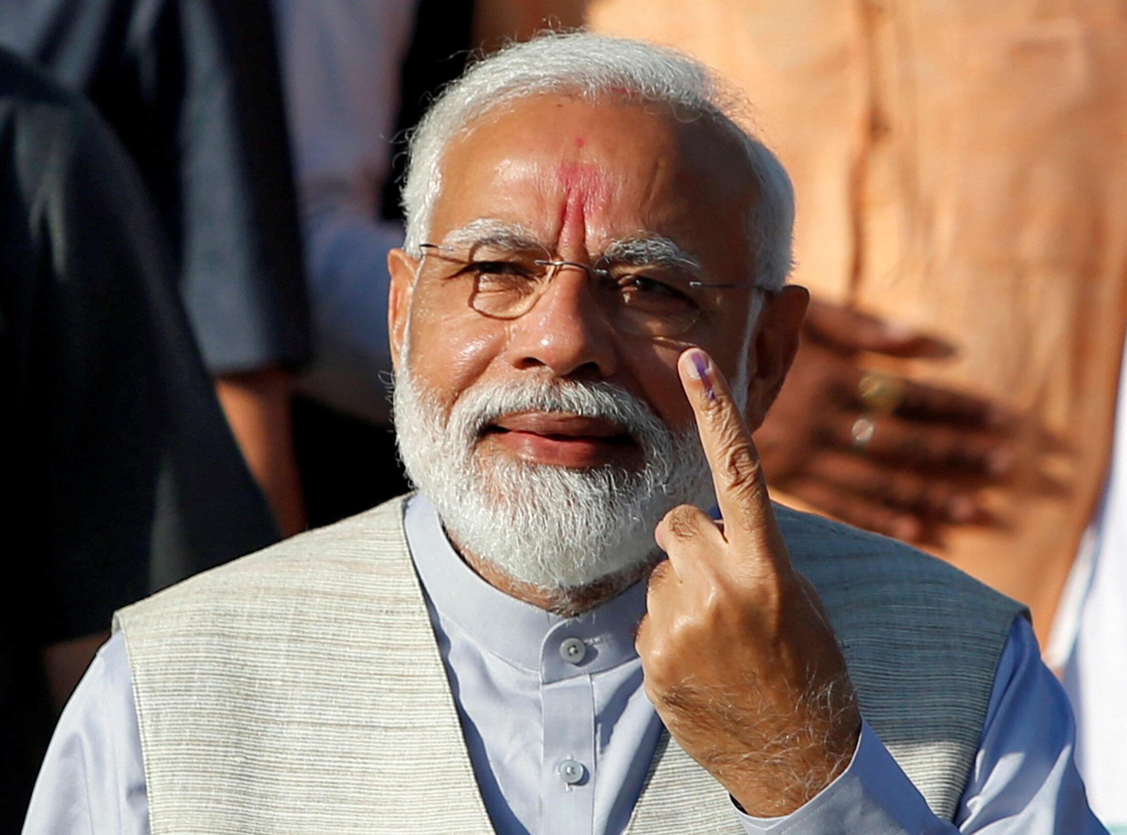 Le Premier ministre indien Narendra Modi montrant son doigt encré, après avoir voté à Ahmedabad dans le Gujarat, le 23 avril 2019.