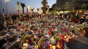 People stand in front of flowers, candles and messages laid at a makeshift memorial in Nice on July 18, 2016, in tribute to the victims of the deadly attack on the Promenade des Anglais seafront