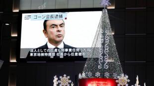 En una pantalla gigante en Japón aparece la imagen deCarlos Ghson en medio de las decoraciones navideñas, el 21 de noviembre de 2018.