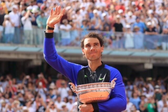 Rafael Nadal agradece ao público abraçado à taça de vencedor de Roland Garros em 11 de junho de 2017