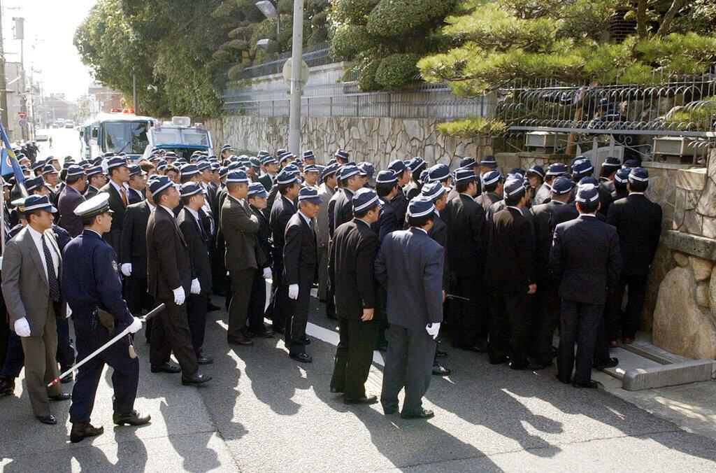 Investigadores de la policía de la prefectura de Osaka entran en la sede del sindicato yakuza Yamaguchi-gumi para una redada en el caso de una acusación de fraude en Kobe, oeste de Japón, el miércoles 15 de marzo de 2006.