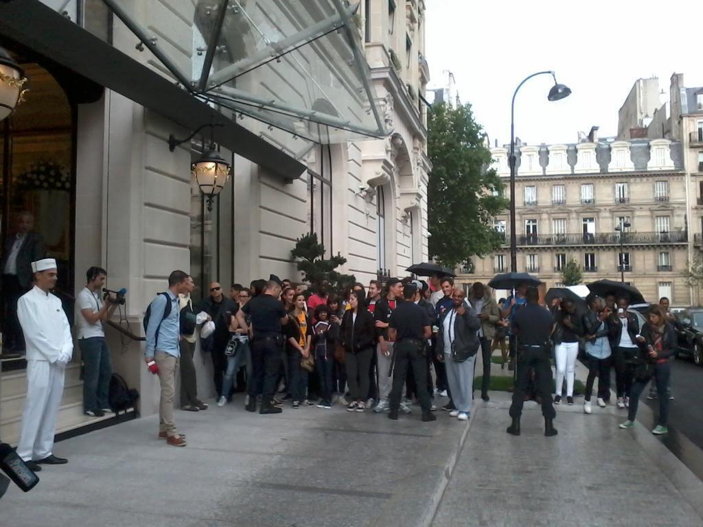 Torcedores do PSG e fãs de David Luiz sob a chuva em frente ao hotel The Peninsula, em Paris.