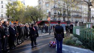 Le président français Emmanuel Macron et la maire de Paris Anne Hidalgo observent une minute de silence devant la plaque commémorative en hommage aux victimes des attentats du 13 novembre 2015.
