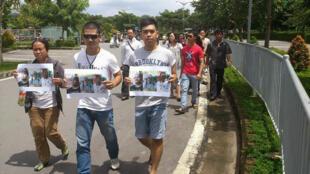Bạn hữu và thân nhân ba blogger bị câu lưu, với ảnh họ trên tay, ra phi trường Tân Sơn Nhất đòi thả người, 06/10/2013. Ảnh danlambaovn.blogspot.com