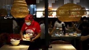 Une employée débarasse la table d'un restaurant de Pékin le 14 août 2020.