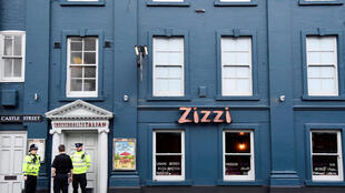 A police officer stands outside a restaurant closed after former Russian intelligence officer Sergei Skripal and his daughter Yulia were found unconscious on a bench in Salisbury, Britain, 6 March 2018.