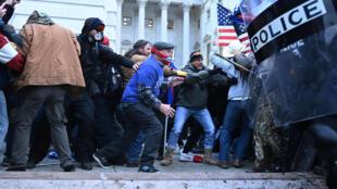 Seguidores del presidente saliente Donald Trump se enfrentan a las fuerzas de seguridad en las afueras del Capitolio en Washington, el 6 de enero de 2021
