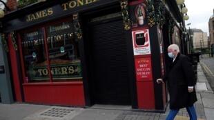 Un homme portant un masque passe devant un pub fermé à Dublin, Ie 1er octobre 2020.