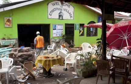 An investigator walks through the remains of an Ethiopian-themed restaurant that was hit by an explosion in Kampala