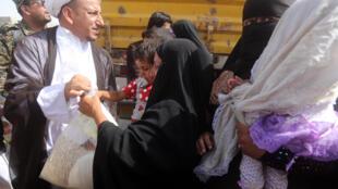 Un représentant d'Ali Sistani, leader spirituel des chiites d'Irak, distribue des vivres le 6 juin dans un camp de réfugiés arrivant de Ramadi, après la prise de la ville par l'organisation Etat islamique.