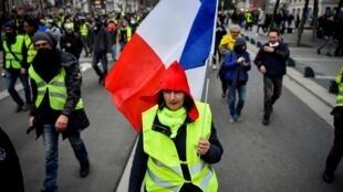 Une «gilet jaune» tient un drapeau français lors d'une manifestation à Nantes, le 12 janvier 2019.