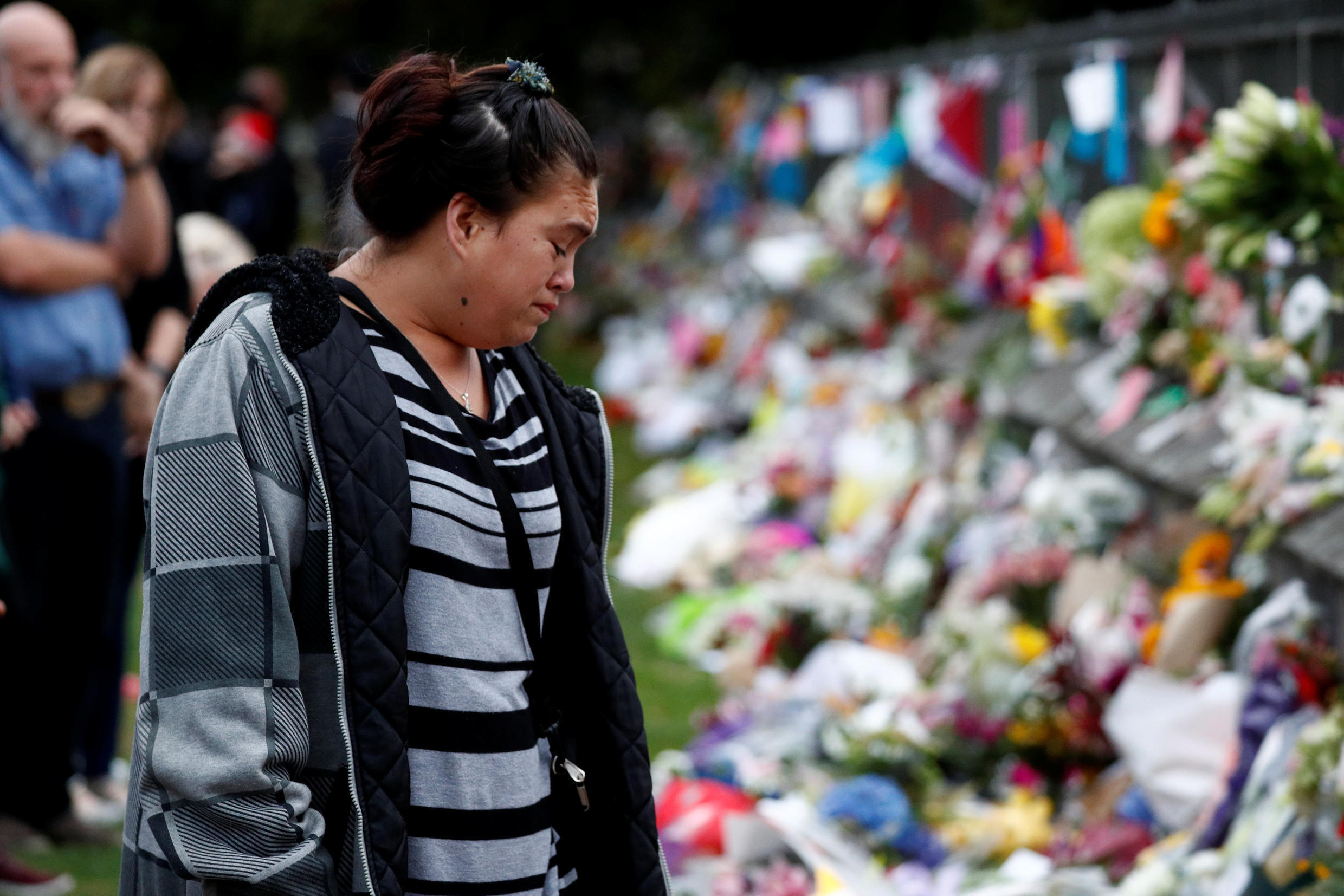 A woman reacts at a flower tribute area at Botanical Gardens in Christchurch, New Zealand, March 16, 2019.