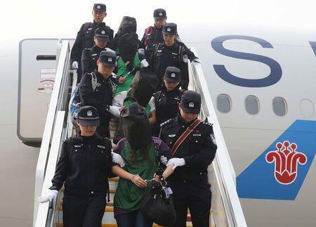 Cảnh sát áp giải một nhóm nghi phạm người Đài Loan bị áp giải từ Kenya sang Trung Quốc, phi trường Bắc Kinh, 13/04/2016.