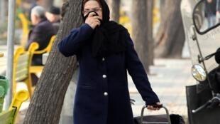 Une Iranienne se couvre la bouche face à la forte pollution atmosphérique de Téhéran, le 15 décembre 2019.