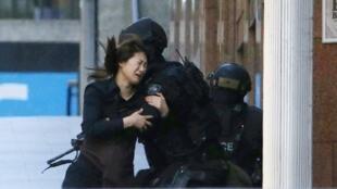 Ảnh phụ nữ chạy thoát được  khỏi quán cà phê Lindt nơi các con tin bị bắt giữ ở trung tâm Sydney, ngày 15/12/2014.