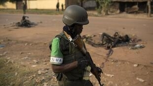 Un soldat de la Misca, lors d'une patrouille à Bangui, passe devant les corps de deux musulmans tués par une foule hostile, le 26 janvier 2014 à Bangui.