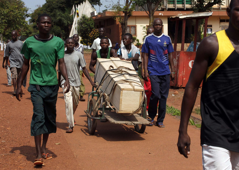 Des hommes transportent un cercueil dans une brouette dans les rues de Bangui, le lundi 9 décembre 2013.