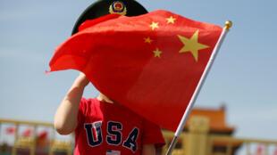 北京街头身着印有USA(美国)字样T恤衫、手持五星红旗的小男孩。2019年5月7日摄于北京。