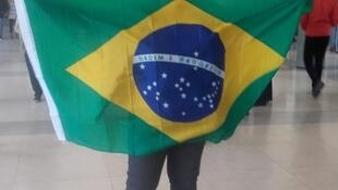 Eleitora exibe a bandeira nacional na Faculdade de Direito de Lisboa, onde brasileiros puderam votar para presidente neste domingo (28).