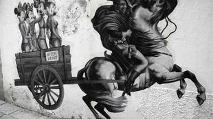 Hình ảnh được dán trên một bức tường ở Milan, với Thủ tướng Silvio Berlusconi trong trang phục của Napoléon điều khiển một cỗ xe ngựa chở các cô gái đẹp. Ảnh chụp ngày 29/9/11.
