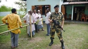 In Assam State, some men wait to see if their names are on the citizenship life while a soldier stands guard. If not and they can susbstantiate their claim, they will have to appeal to special foreigner tribunals. 31 August 2019